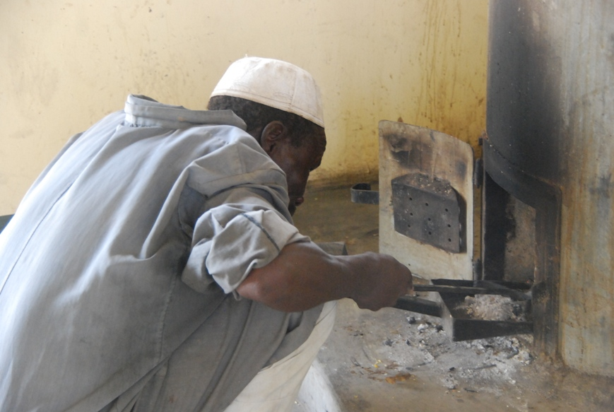 Cook, Kierko, removing ash from one of the stoves