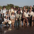 Students in the Journalism Without Walls program, along with their professors (Ilana Ozernoy, kneeling second from left, and Barbara Selvin, standing second from right) and translators from TBI, pose in the middle of crossing the Turkwel River, which flows beneath the institute. TBI Director Lawrence Martin, standing third from left, helped team members through the deepest stretch of the crossing.