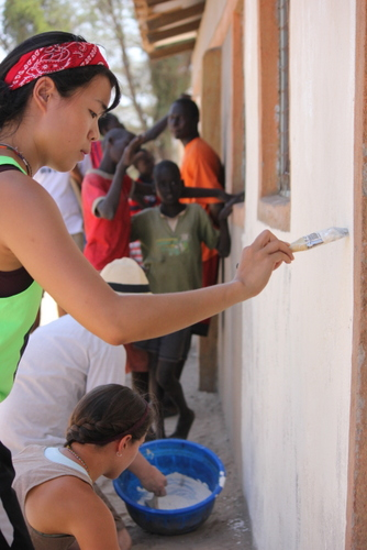 Students applying a white base coat to the Primary School walls