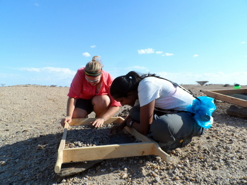 Kathleen and Vaishnavi study the sediment scrupulously