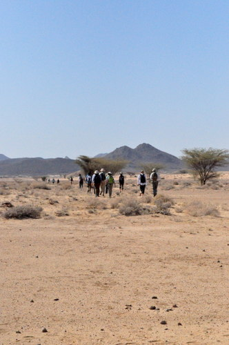 Students walking across the desert towards the Napedet Hills
