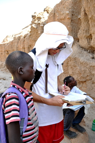 One of the Turkana children stops by on the way back from school and takes a peek at Rob's notes.