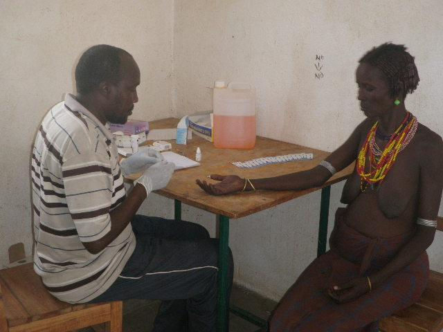 Tbi mobile clinic staff Lochudang Imoi attending to a woman at the Ileret health centre