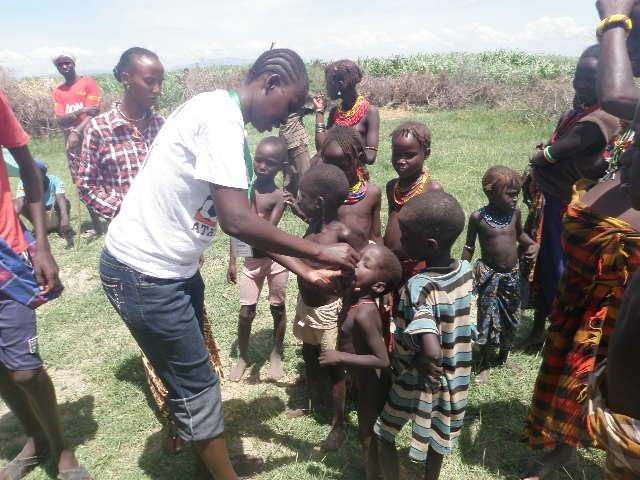 Nurse Beatrice Eyomo giving polio drops to children in Nangolei village