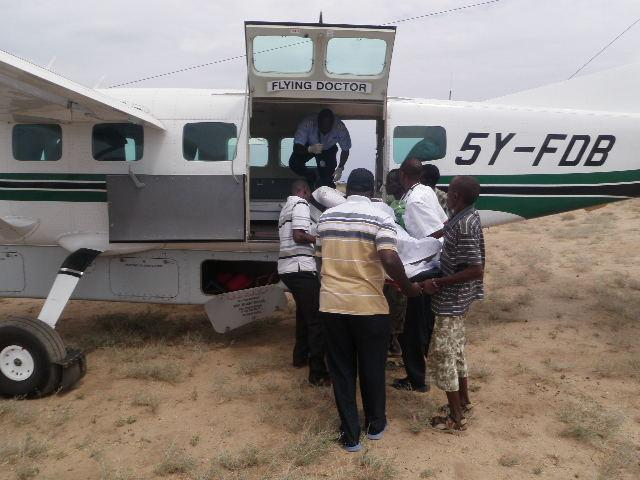 TBI staff helping a patient get on a plane through the flying doctors services.
