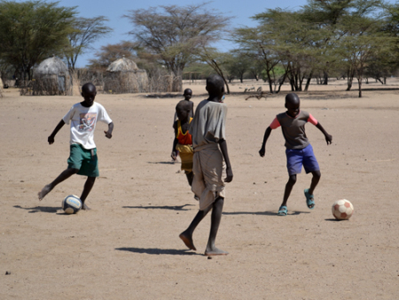 Local Turkana boys play a game of their own on the sidelines.