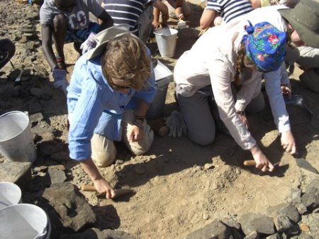 Lucy and Eloise use their trowels to make the rest of the site level with the skeleton.