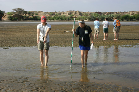 Larisa points out a change in channel topography while Rachel measures the depth.