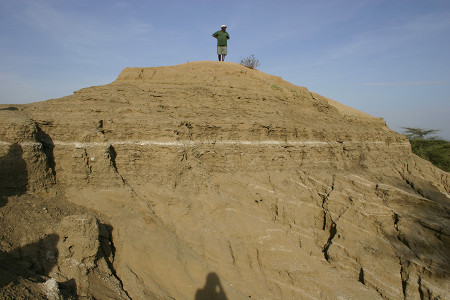 Our driver Erasmi poses on top of Holocene lake beds at Epim. The angled beds in the bottom half of the picture are did not form from faulting. Instead the sedimentary followed the topography of the past landscape similar to the slope of this modern hill.