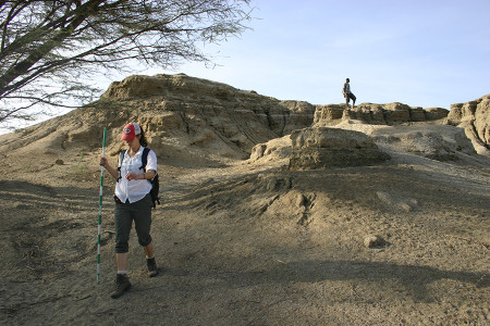 Larisa marches down the hill to take a better look at the outcrop and create a sketch before beginning her measurements.