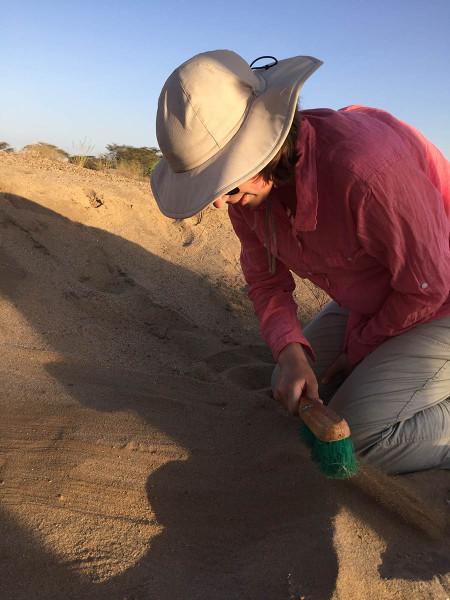 After documenting and collecting a pottery shard from the surface, Kate proceeds to slowly brush aside sediment on the surface in the hopes of finding more pieces.