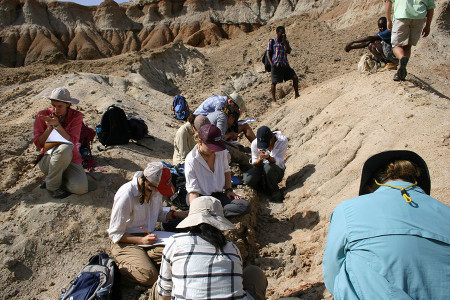 TBI students examine the sediment that is found around the fossil. Kate (in pink), a geology major, identifies several minerals in the sediment.