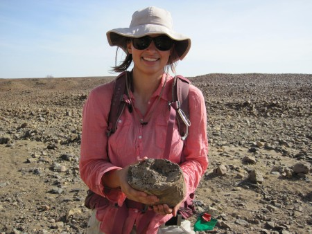 Kate picks up a chunk of petrified wood. This environment was quite different from today.