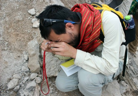 Ryan uses a hand lens to look closely at the glass particles in the tuff.