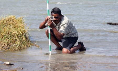 Tadele levels the jacobstaff with a brunton compass. This will provide one accurate data point to measure changes in elevation going from the shore into the water.