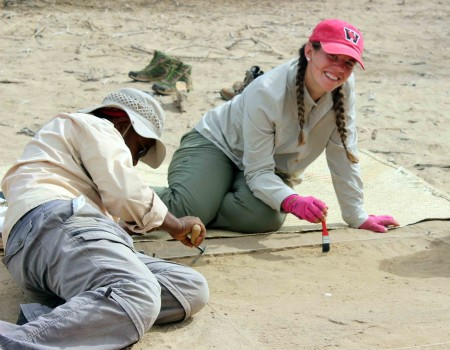 Jen and Tadele carefully brush off the surface of their excavation square.
