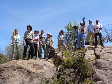 Kimani points out to the students how vegetation in the compound is much more dense than outside of the compound