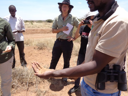 Kimani discusses how the soil is mostly composed of sand and in order to stress this he conducts a mini experiment in the field