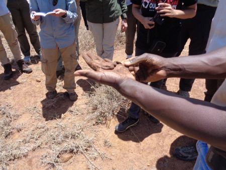 Kimani showing the students how adding water to the sandy soil can help one determine how much clay is present. The less clay, the less the soil will stick together.