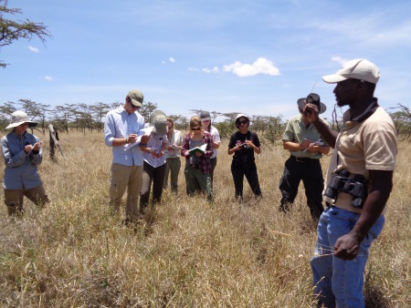 Kimani shows the students how around termite mounds there are various species of grass